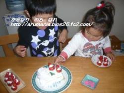 ケーキ(実はス○スロールにデコってるだけ!)にいちごサンタ・ピンクアラザン(100均で発見)をトッピング中。