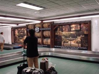 ジャックダニエルの宣伝を見ながら荷物を待つ