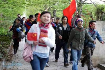 中国旗を持つ人間と仲良く歩くチベット人(?)