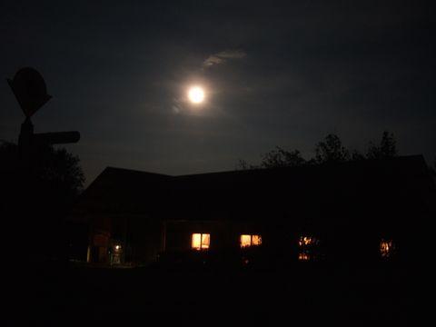 輝く満月と宿泊客用のロッジ。天文台は開閉式になっている。